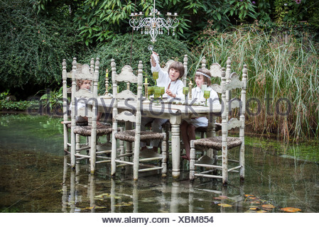 Children seated at ornate dining table floating on lake - Stock Photo
