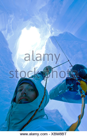 A skier who fell down a crevasse while travelling on a glacier in the Darwin Range, Chile, is in a tricky situation - Stock Photo