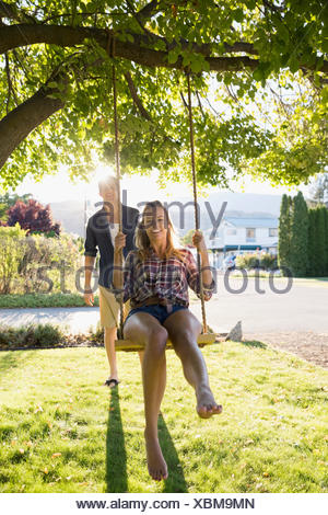 Young couple swinging at tree swing in sunny summer yard - Stock Photo