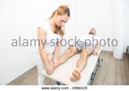 Physiotherapist helping patient to do leg exercise - Stock Photo