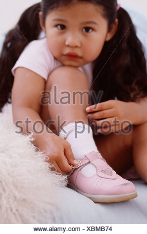 Female toddler with brunette hair, wearing a pink t shirt, buckling shoe, looking at camera Ian Boddy - Stock Photo