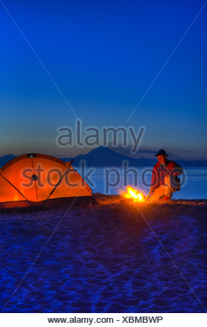 Man sitting at campfire with Cook Inlet and Mt. Redoubt in the background, Kenai Peninsula, Southcentral Alaska, Spring - Stock Photo