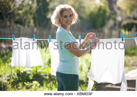 A mature woman pegging out washing on a washing line, smiling - Stock Photo
