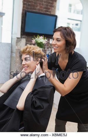 Hairdresser cutting a customers hair - Stock Photo