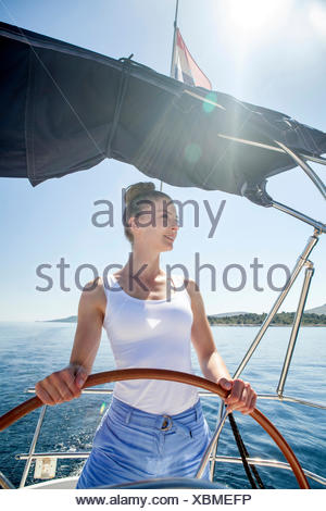 Young woman steering on sailboat, Adriatic Sea - Stock Photo