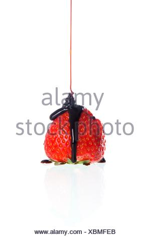 Cascade of chocolate on a strawberry - Stock Photo