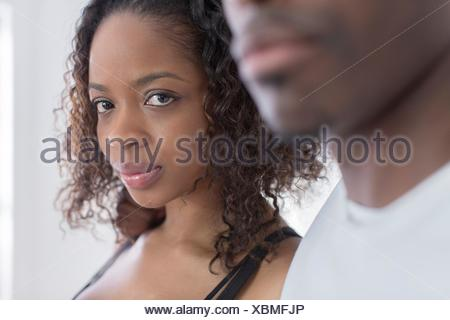 Studio portrait of confident young woman next to boyfriend - Stock Photo