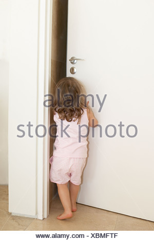 Young girl pushing open a door - Stock Photo