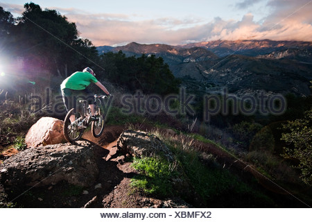 A young man rides his downhill mountain bike on Knapps Castle Trail, surrounded by beautiful scenery in Santa Barbara, CA. - Stock Photo