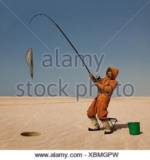 Eskimo catching fish in desert - Stock Photo