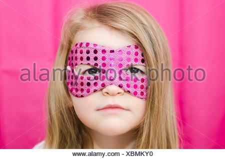 Portrait of a girl wearing a superhero mask - Stock Photo