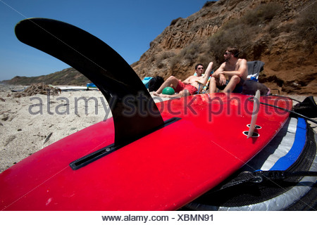 Two men lounging on the beach with a surfboard prominent in the foreground. - Stock Photo