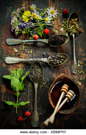 Various kinds of tea with honey, wild berry and flowers on wooden background - Stock Photo