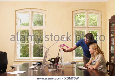 Young man helping young woman working on computer in living room - Stock Photo