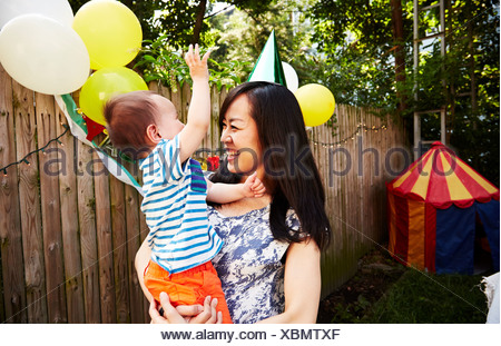 Mother wearing party hat holding baby boy at birthday party - Stock Photo