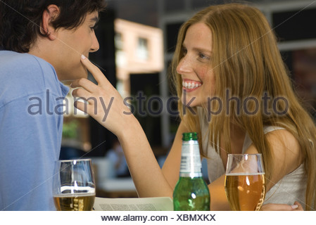 Young couple in cafe, woman touching man's cheek - Stock Photo