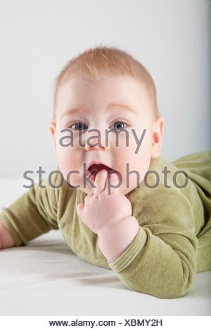 six months age blonde baby green velvet onesie lying on white sheet bed smiling happy face. - Stock Photo