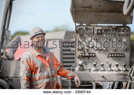 Drilling rig worker in hard hat and workwear, smiling - Stock Photo