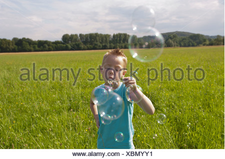 Germany, North Rhine-Westphalia, Hennef, Boy blowing bubbles from bubble wand in meadow - Stock Photo