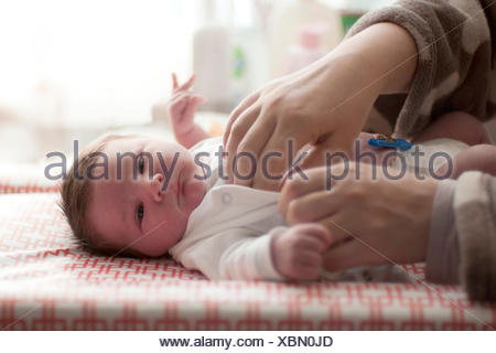 Baby being dressed by parent, cropped - Stock Photo