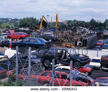 Wrecking yard, scrapyard, cars and electric locomotives, recycling, metal salvaging - Stock Photo