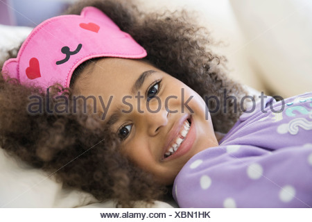 Portrait of cute girl wearing eye mask - Stock Photo