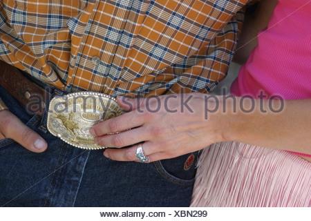 Girl Touching Mans Belt Buckle - Stock Photo