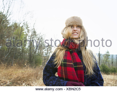 A woman in a warm furry hat and a big red tartan scarf outdoors in the winter - Stock Photo