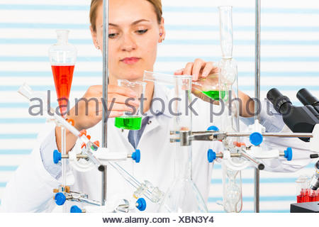 MODEL RELEASED. Female chemist pouring chemicals into glassware in laboratory. - Stock Photo