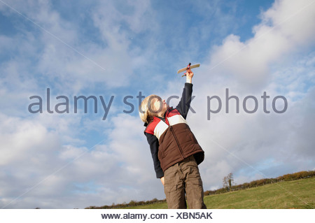 Young boy with toy plane in countryside - Stock Photo