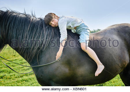 Cropped shot of boy leaning forward with eyes closed on horse in field - Stock Photo