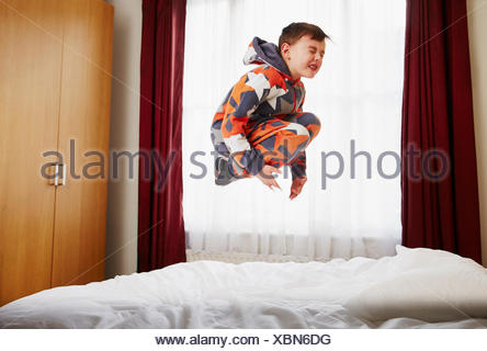Young boy jumping on bed - Stock Photo