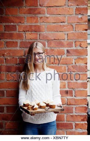 Sweden, Uppland, girl (14-15) with cupcakes against brick wall - Stock Photo