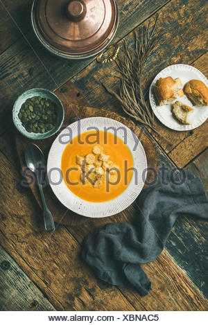 Flat-lay of fall warming pumpkin cream soup with croutons and seeds on board over rustic wooden background, top view, vertical composition. Autumn veg - Stock Photo