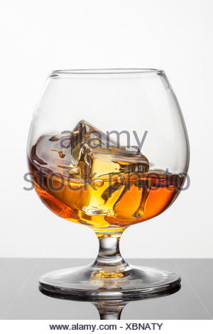 Splash of whiskey with ice in glass isolated on white background. Raw photo - Stock Photo