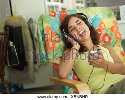 Teenage girl 15 17 sitting in armchair at home listening to MP3 player singing eyes closed - Stock Photo