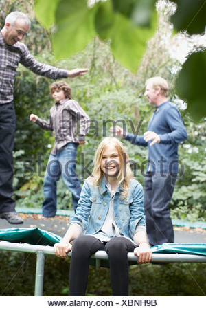 Family jumping on trampoline - Stock Photo
