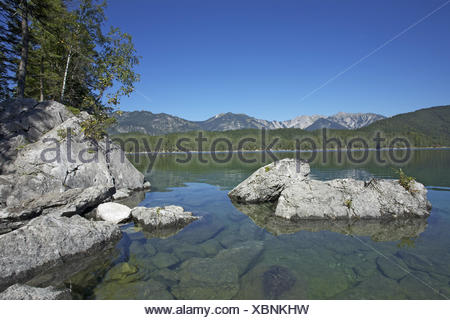 Eibsee with Grainau close Garmisch-Partenkirchen, rock on the east shore, view at Ammergebirge with cross point, 2185 m, - Stock Photo