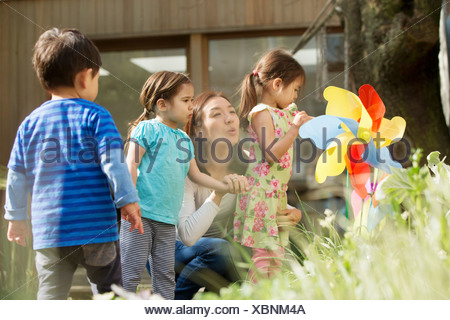 Mother and three children with toy windmill in garden - Stock Photo
