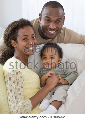 Portrait of parents and baby on sofa - Stock Photo
