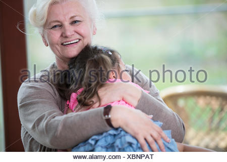 Portrait of happy grandmother hugging granddaughter in house - Stock Photo