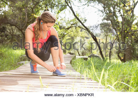 Blonde athlete tying shoelace on wooden trail - Stock Photo