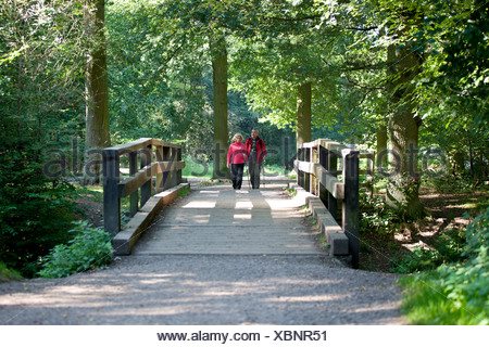 A mature couple walking over a footbridge in the countryside - Stock Photo