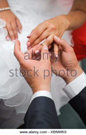 Bridegroom put the ring on one's finger of bride - Stock Photo