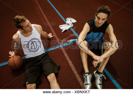 Portrait of two young basketball players relaxing on basketball ground - Stock Photo