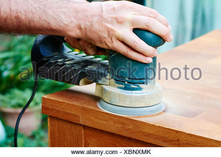 Man sanding an oak table with a random orbital sander, close-up - Stock Photo