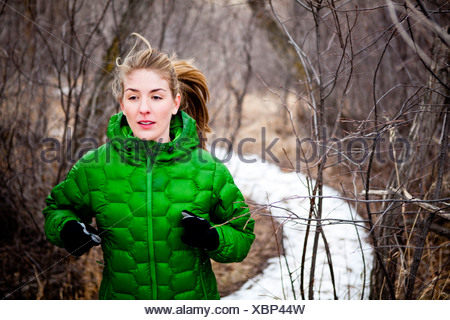 a young woman runs a along snow covered dirt trail through leafless deciduous trees just north of Dixon Reservoir, on a cold day - Stock Photo