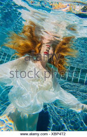 Young woman underwater, wearing thin white shirt - Stock Photo