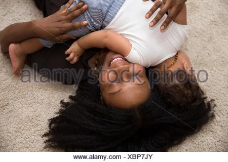 Mid adult woman hugging toddler daughter on rug - Stock Photo
