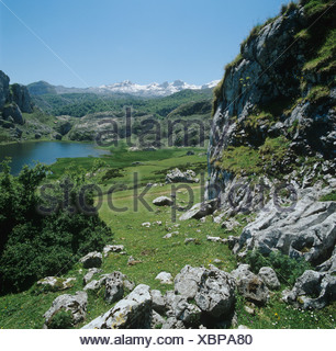 Lago de la Ercina and the snow capped mountains of the Picos de Europa Spain - Stock Photo
